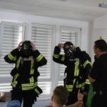 Die Feuerwehrmänner setzen ihr Atemschutzgerät auf.